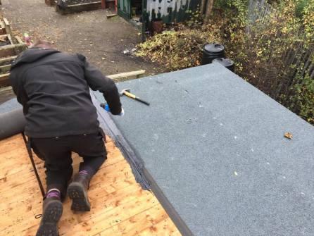 Volunteers re-felting the roof
